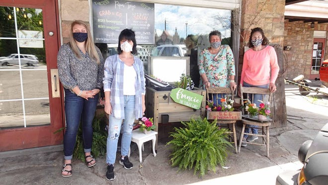 The team at Paper Twigs in Jackson Township (from left) Lucy Burk, Renata Luntz, owner Laura Woofter and Tara Lockwood. They are standing next to the floral cart where people can buy flowers without having to go into the shop.