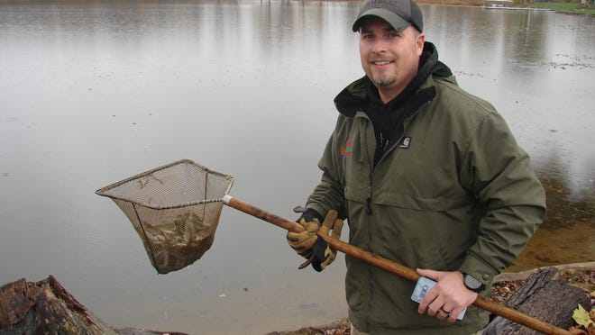Chase Haylett puts in some of the 200 walleye stocked in Mud Lake Tuesday.