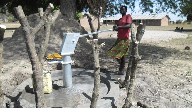 Acio Nancy, a former pupil of Ajobi Primary School in northern Uganda, fetches water from a newly-drilled borehole at the school.