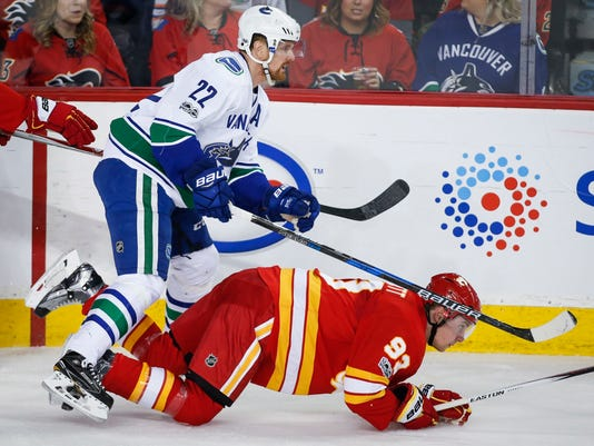 Vancouver Canucks' Daniel Sedin, left, of Sweden, knocks over Calgary Flames' Sam Bennett during the second period of an NHL hockey game, Saturday, Jan. 7, 2017 in Calgary, Alberta.  (Jeff McIntosh/The Canadian Press via AP)