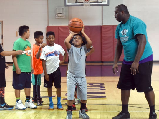Members of the Rebirth of Camden play basketball at area gyms. Zy'Aire Tart gets ready to shoot a free throw with advice from Tyheem Baker. Other kids in the photo are, from left to right: Jacier Procter; James Procter, Jr.; Zoé Holman; and Dwayne Smith. Photo by April Saul