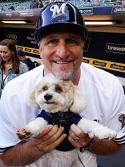 Brewers third base coach Ed Sedar holds his dog, Squirt.