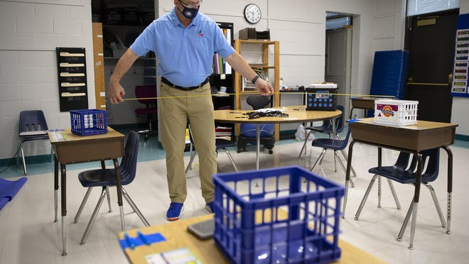 Jason Wind, Director of School Support for District 186, uses a tape measure to check the distance between desks as he does a walk-through with Principal Patricia Nikson to go over plans for in-person learning at Fairview Elementary School, Friday, August 7, 2020, in Springfield, Ill.