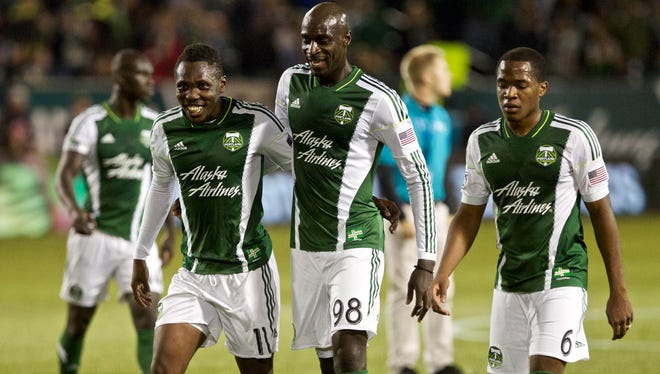 Portland Timbers midfielder Kalif Alhassan, left, celebrates with teammates after scoring a goal just before the first half expired at Jeld-Wen Field.