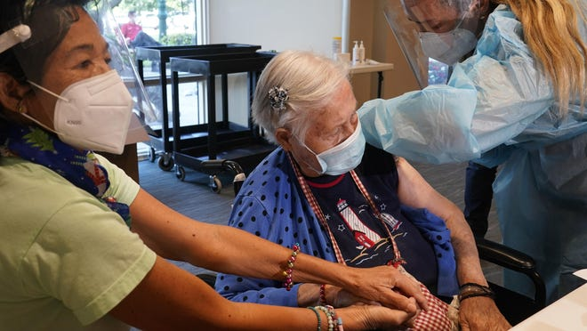 Patricia Wasseman holds Hermina Levin's hands as nurse Eva Diaz administers the COVID-19 vaccine Wednesday at John Knox Village in Pompano Beach, Florida.