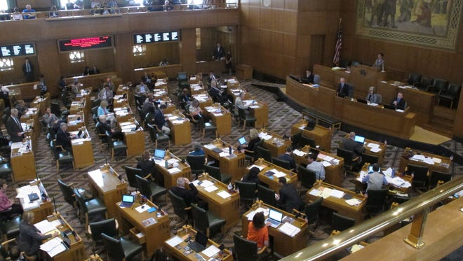 Lawmakers in the Oregon House discuss a bill that would require background checks for private gun sales during a debate at the state Capitol in Salem, Ore., Monday, May 4, 2015.  The bill would make Oregon the eighth state to require universal background checks.(AP Photo/Jonathan Cooper)