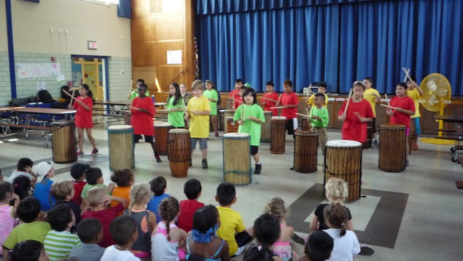 Children perform West African drumming at the end of their summer camp at Claremont School.