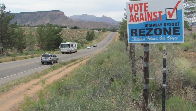 Vehicles pass a sign encouraging voters to overturn a town ordinance in Virgin in this June file photo at the site of a land parcel a company wants to turn into an RV resort in the highway corridor leading to Zion National Park.