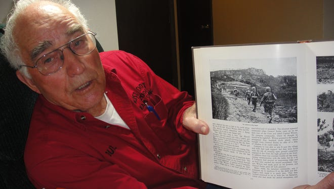 """Retired Buffalo rancher Durl Gibbs shows a picture of the battle to take the """"Big Apple,"""" a ridge on Okinawa, Japan, during World War II."""