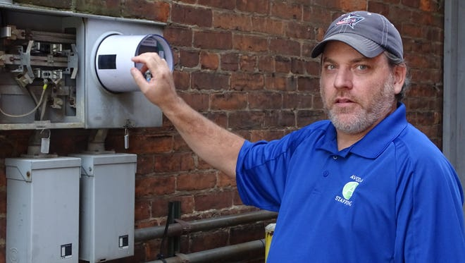 Frank Millard, co-owner of Avodah Staffing and Recruiting, points to the spot the stolen meter was.