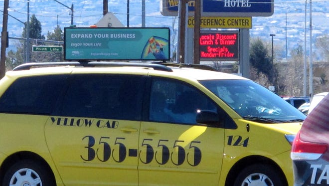 In this photo taken March 13, 2015, a Yellow Cab taxi waits in a staging area at Reno-Tahoe International Airport. A legal battle over a discrimination lawsuit a former Nevada taxi driver and his disabled wife filed against Yellow Cab of Reno nearly three years ago is in limbo after the company filed for Chapter 11 bankruptcy protection.