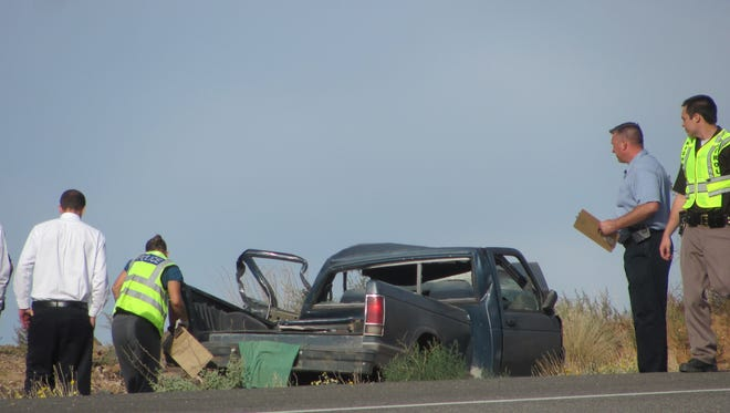 Investigators look at the wreckage of a blue pickup involved in a fatal collision Thursday morning about two miles north of the Snow Canyon Parkway exit on State Route 18. The driver of the pickup was killed after reports he was crossing into oncoming traffic and struck a Washington County employee's truck.