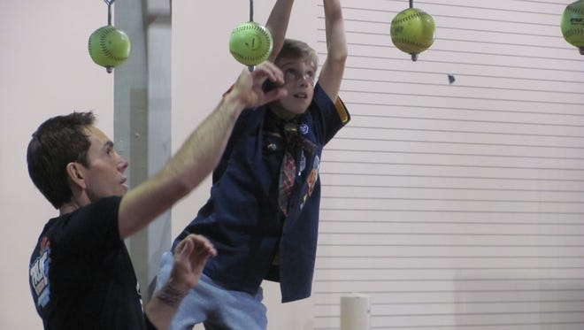 American Ninja Warrior competitor Jon Stewart, of Washington City, coaches Webelos Scout Nic Lucia across a series of hand-grip obstacles Feb. 20, 2016 during the annual Dixie Scout Expo at the Dixie Center in St. George.