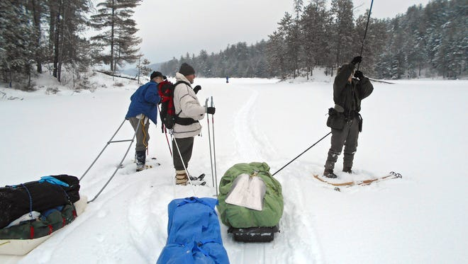 Dick Shank of St. Paul, right, reassembles his sled pull fiberglass rod as Cory Kolodji, left, and Chuck Rose look on. The group walked about 1.5 miles to the camp site.