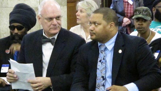 Atlantic City Mayor Don Guardian, at left, consults with City Council President Marty Small before testifying at a hearing in Trenton against a planned state takeover of the seaside gambling resort.