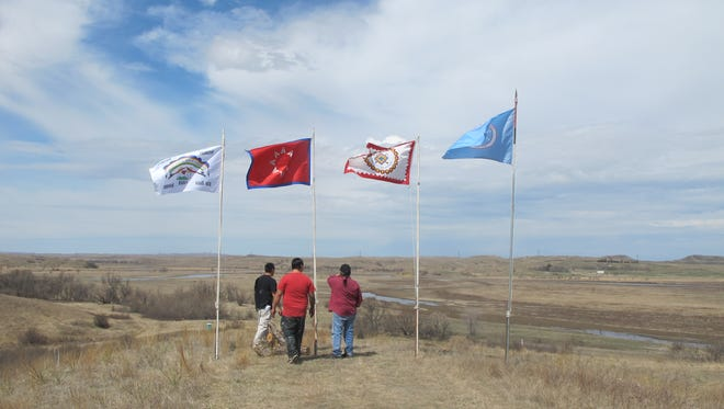 Mikal White Mountain, left, Hoksila White Mountain, center, and Eddie Brown, all of McLaughlin, S.D., stopped at the flags overlooking the Standing Rock Sioux protest camp earlier this month at the confluence of the Cannonball and Missouri rivers, near Cannon Ball, N.D.