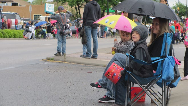Parade-goers with a sunny disposition find shelter from cool, rainy weather Saturday at Washington City's annual Cotton Days festivities.