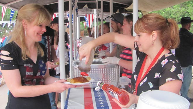 Faye Cox, right, serves syrup and ketchup as part of a free community breakfast Saturday at Colorado City's Cottonwood Park. Residents and numerous out-of-town visitors held the community's Fourth of July celebration Saturday to kick off the holiday weekend.
