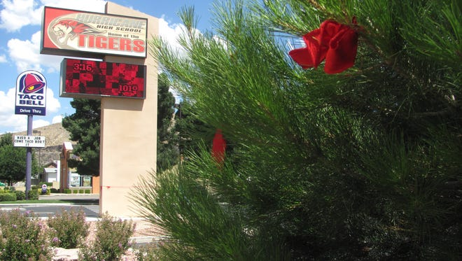 Red ribbons are tied in the trees at Hurricane High School on Monday in honor of Pierce Adamson, a 15-year-old student who fell to his death Sunday night as he and a family member were hiking on the cliffs north of Hurricane's airport.