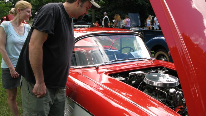 Darren Zeller of Fishkill, 46, and his wife, Ivonne, 39, look over a 1961 Chevrolet Corvette during the 11th Annual David Hill Memorial Locust Grove Car Show in Poughkeepsie Sunday.