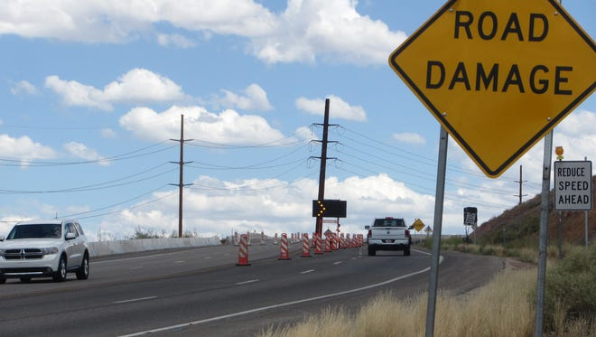 Road signs indicate an area of damaged roadway Saturday as traffic climbs Washington City's Telegraph Street toward the Coral Canyon subdivision. The city is working toward a lasting fix for the zone where earth movement has made repeated repairs necessary.