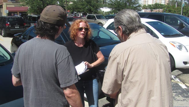 Clinton volunteer Theresa Darlington (center) tries to register George Almond (right) for the Nov. 8 election. Standing with them outside the Social Security office in St. Petersburg is Almond's son, Shawn.