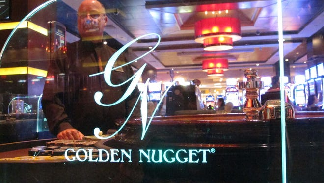 A dealer works behind the glass of a roulette table at the Golden Nugget casino in Atlantic City in June.