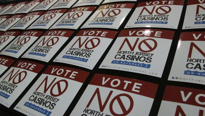 Stickers opposing a referendum on whether to allow two new casinos in northern New Jersey sit on a table before a rally in Atlantic City Thursday.
