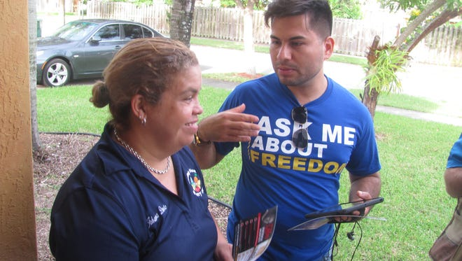 esar Grajales, Florida state director of the Libre Initiative, speaks with Johanna Duarte outside her home at the Villas de Campo community in Homestead, Fl. His organization is looking to convince potential swing Hispanic voters to support GOP Sen. Marco Rubio this election