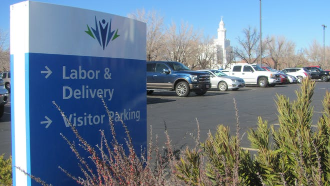A parking lot sign at Dixie Regional Medical Center's 400 East campus directs visitors to stalls near The Church of Jesus Christ of Latter-day Saints' iconic St. George temple.
