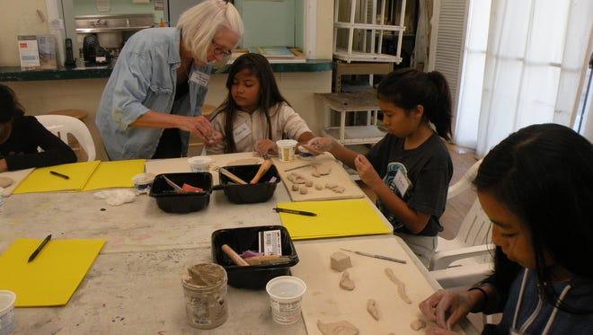 Middle school students work on art projects with a Desert Art Center member-teacher.