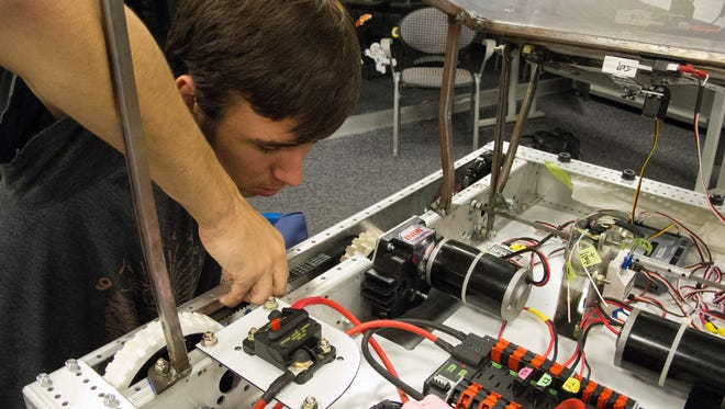 Joseph Goyer takes measurements to make a computer model of Goddard so the team can continue to work after the robot is sealed in a bag in accordance with FIRST rules.