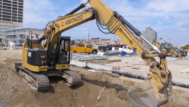 A heavy equipment operator digs dirt from a trench near the Atlantic City Boardwalk on Thursday for the new satellite campus of Stockton University and South Jersey Gas.