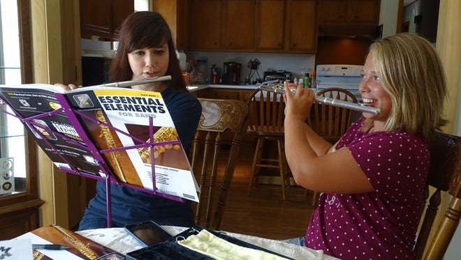 """Hannah Schlichting, left, and Marissa Stephens, right, start the lesson with an exercise to practice breath support - holding a note for 10 seconds. """"I didn't even make it to three,"""" 11-year-old Stephens said."""