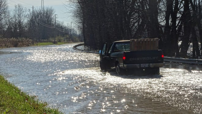 A man tried to drive his truck through high water on Ohio 203 before stopping and backing out Monday. The road remained closed Monday after heavy rains Saturday caused flooding from the neighboring Scioto River.