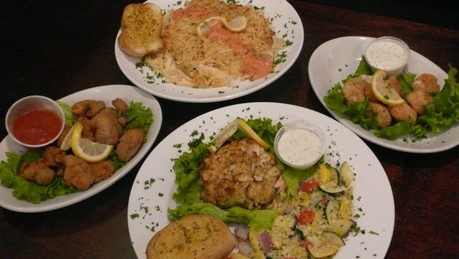 Flounder Florentine and crab cakes, shown here with oyster and scallops appetizers, are among the seafood offerings at Cheers Sports Bar & Grill.