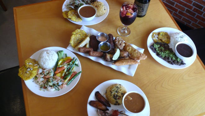 Centered around a Sampler Platter are some of the specialties at Latin Flavor. Clockwise from top are Carne Frita, Churrasco, Pernil and Camarones al Ajillo.