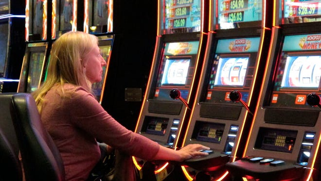 A woman plays slot machines at Resorts Casino Hotel in Atlantic City. As Atlantic City's casinos mark their 40th anniversary, the industry is hailing the reopening of two of the five casinos that shut down since 2014. But some worry that re-expanding the market could lead to the same conditions that caused the wave of closings in the first place.