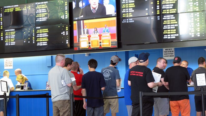 Bettors line up at windows at Monmouth Park racetrack in Oceanport to make sports bets. Monmouth Park and Atlantic City's Borgata casino say they're pleased with the extra revenue sports betting has brought in during the first few days it has been legal in New Jersey.