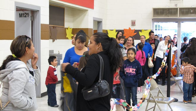 Families line up to get a fresh meal at Zuri's Circle Feeding the Community event at Cesar Chavez Community School on November 16, 2014.