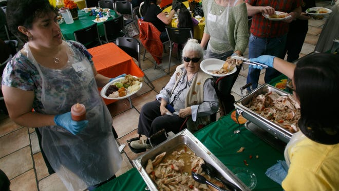 Volunteers serve traditional Thanksgiving fare to community members at an annual community Thanksgiving dinner.