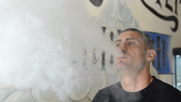 Matthew Nathan, owner of Vapeology on Raymond Avenue in the Town of Poughkeepsie, vapes.