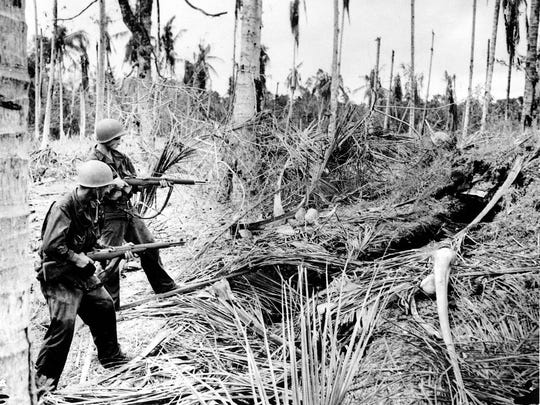 January 1943: Two American soldiers of the 32nd Division cautiously fire into a Japanese dugout before entering it for inspection during a drive on Buna, which resulted in a defeat of Japanese forces in the Papaun peninsula of New Guinea during World War II.