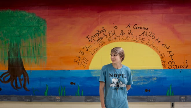 Riverview East sophomore Gracy Minor, 15, stands near a mural she worked on with middle school students during a study hour with teacher Andrea Heaslip Friday, June 2, 2017 at Marine City Middle School.