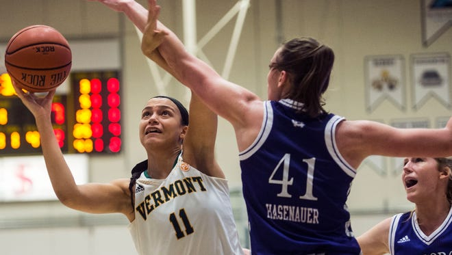 UVM #11 Candice Wright gets around Holy Cross #41 Amy Hasenauer to score during the University of Vermont women's basketball 63-52 win at Patrick Gymnasium Wednesday night, Nov. 30, 2016.