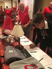 Buckeye fans placed bids on several items up for silent auction at Monday's Beat Michigan Buckeye Bash.