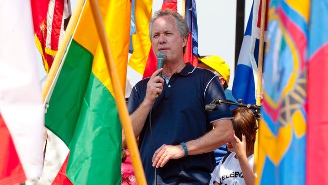 Surrounded by the flags of 56 nations, Louisville Metro Mayor Greg Fischer greets guests at the 13th annual WorldFest celebration on the Belvedere in downtown Louisville.05 Sept 2015