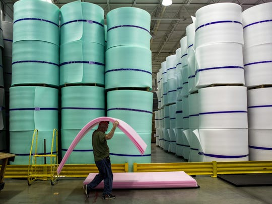 A worker carries planks of foam at Rex Performance
