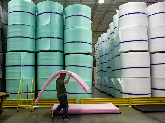 A worker carries planks of foam at Rex Performance Products in Marysville