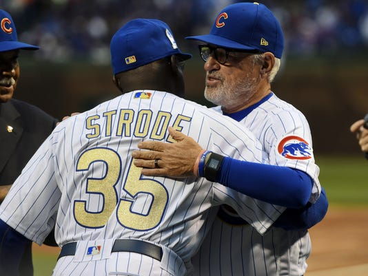 Chicago Cubs' manager Joe Maddon, right, and Chicago Cubs bullpen coach Lester Strode (35) hug as the team celebrates during the 2016 World Series championship ring ceremony before the team's baseball game against the Los Angeles Dodgers on Wednesday, April 12, 2017, in Chicago. (AP Photo/Matt Marton)